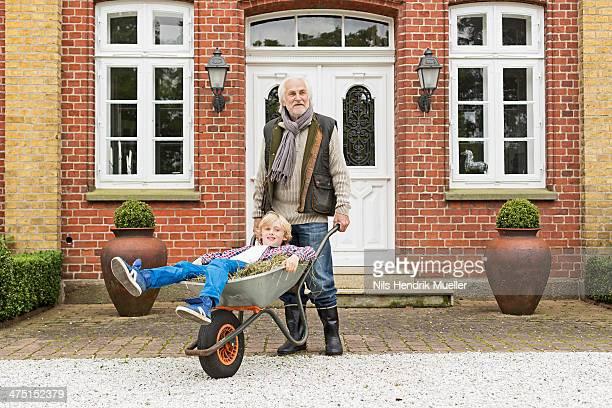 Grandfather pushing grandson in wheelbarrow