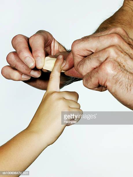 Grandfather putting plaster on grandson's (6-7) finger, close-up