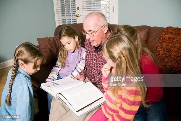 Grandfather Reading a book to grandchildren
