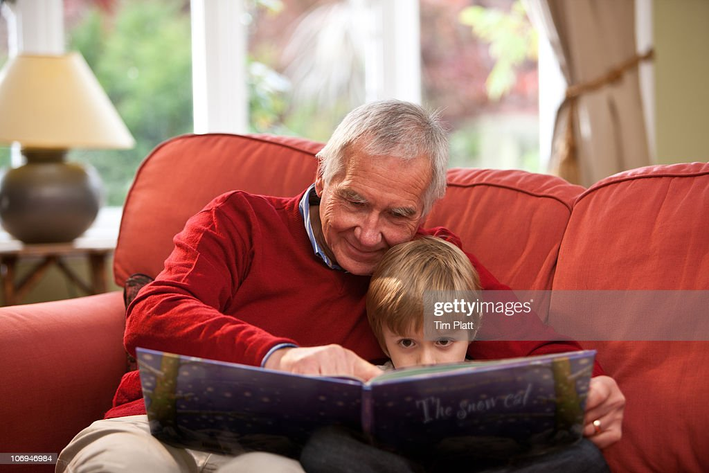 Grandfather reading a book to his grandson (5). : Stock Photo