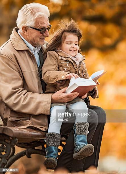 Großvater lesen ein Buch für kleine Mädchen.