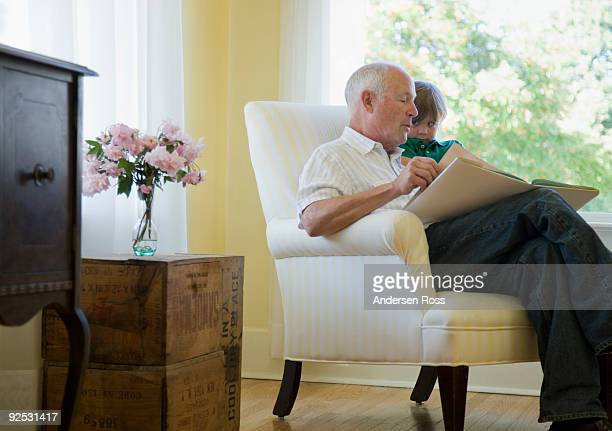 Grandfather reading book to boy