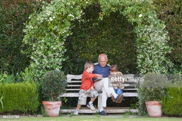 Grandfather reading book to grandchildren on garden bench