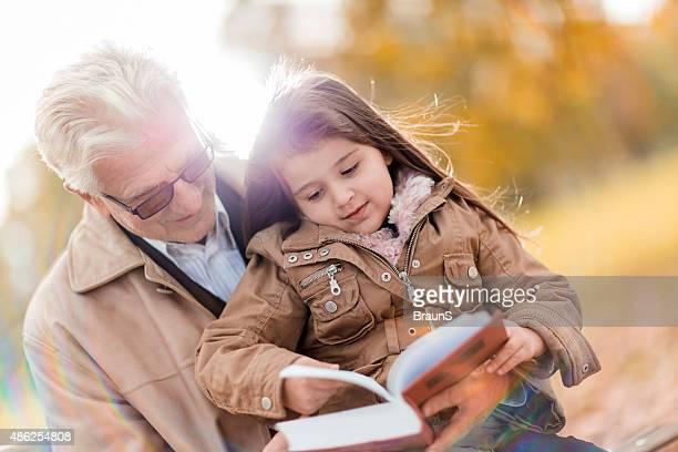 Großvater lesen Geschichten für seine kleine Enkelin in der Natur.