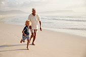 Grandfather Running Along Beach With Grandson On Summer Vacation