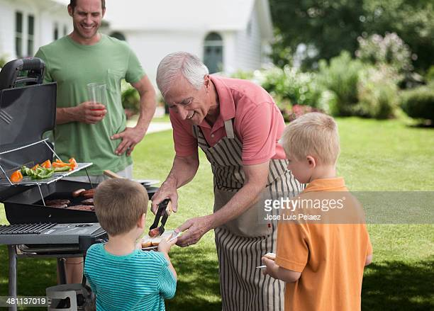 Grandfather serving hot dogs to children