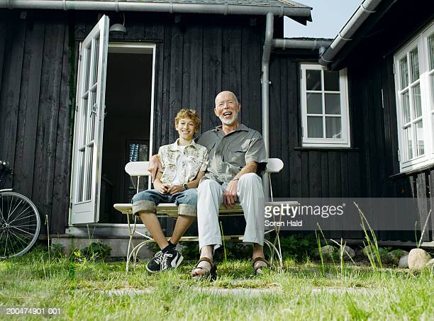 Grandfather sitting in garden with grandson (10-12) smiling, portrait