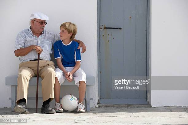 Grandfather sitting outside house with grandson (11-13) on bench