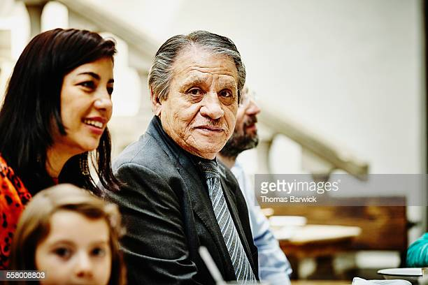 Grandfather sitting with family in restaurant