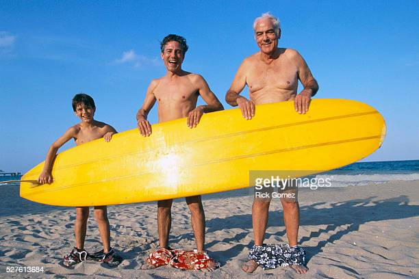 Grandfather, Son, and Grandson Hiding Behind Surfboard