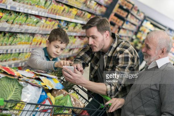 Grandfather, son and grandson in supermarket