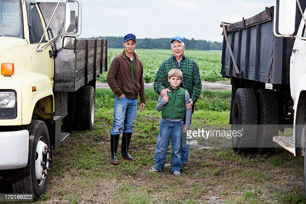 Großvater, Sohn und ihr Enkel in family farm mit LKWs