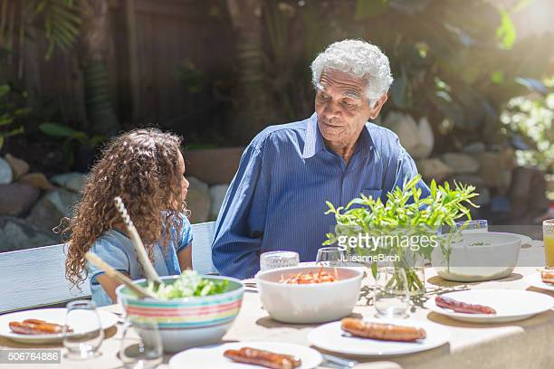 Grandfather talking to grandchild over lunch