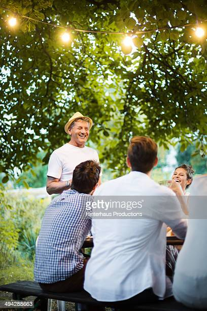 Grandfather Talking To His Family At a Garden Part