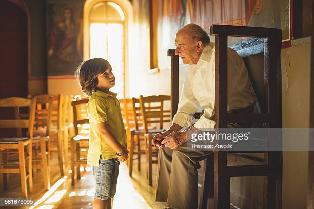 Grandfather talking to his grandson in a church