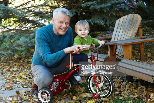Grandfather teaches Grandson to ride tricycle