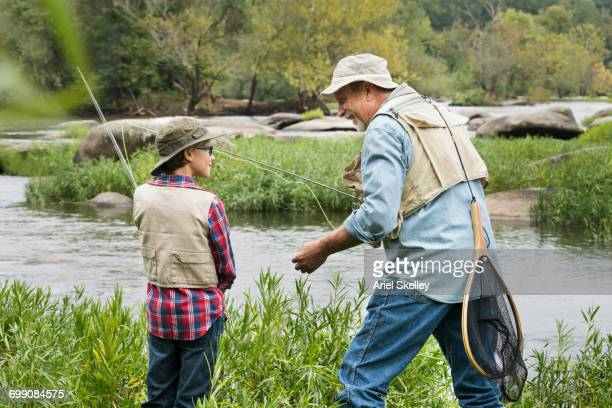 Grandfather teaching fishing to grandson
