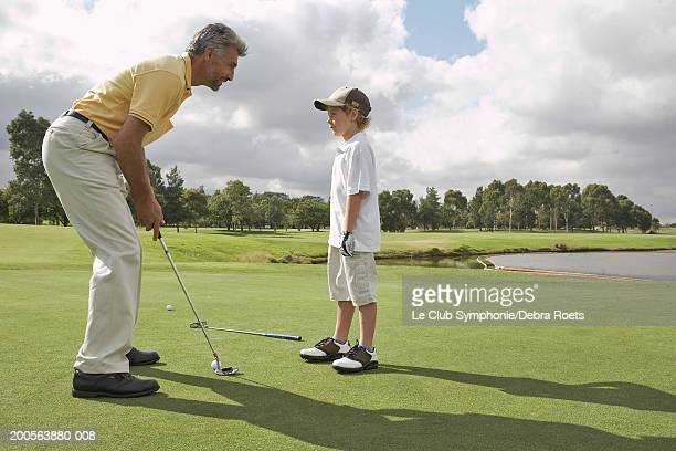 Grandfather teaching golf grandson (8-9), side view