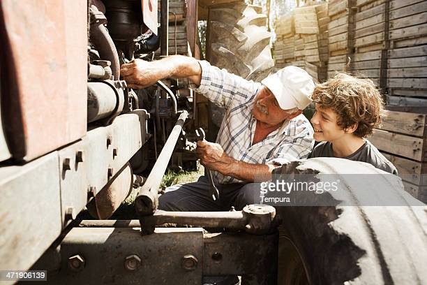 Grandfather teaching grand son how to fix tractor.