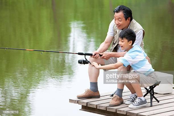 Grandfather teaching grandson fishing