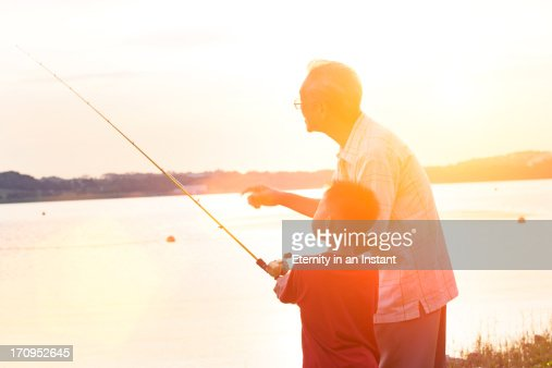 Grandfather teaching grandson how to fish