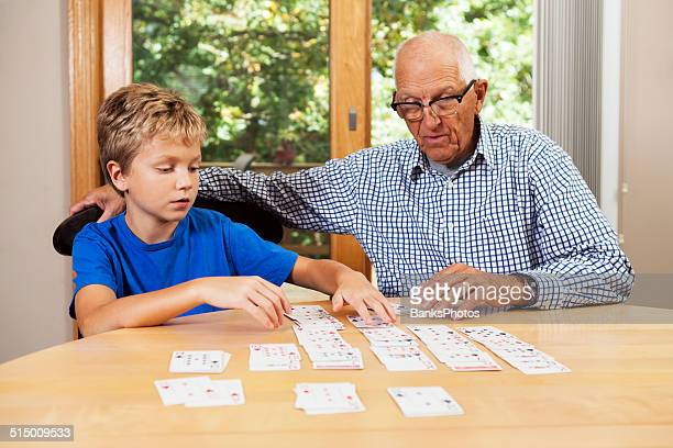 Grandfather Teaching Grandson Solitaire Playing Card Game