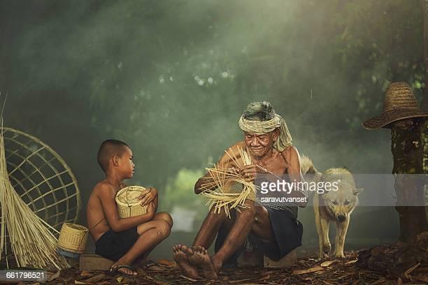 Grandfather teaching grandson to make wicker fishing basket