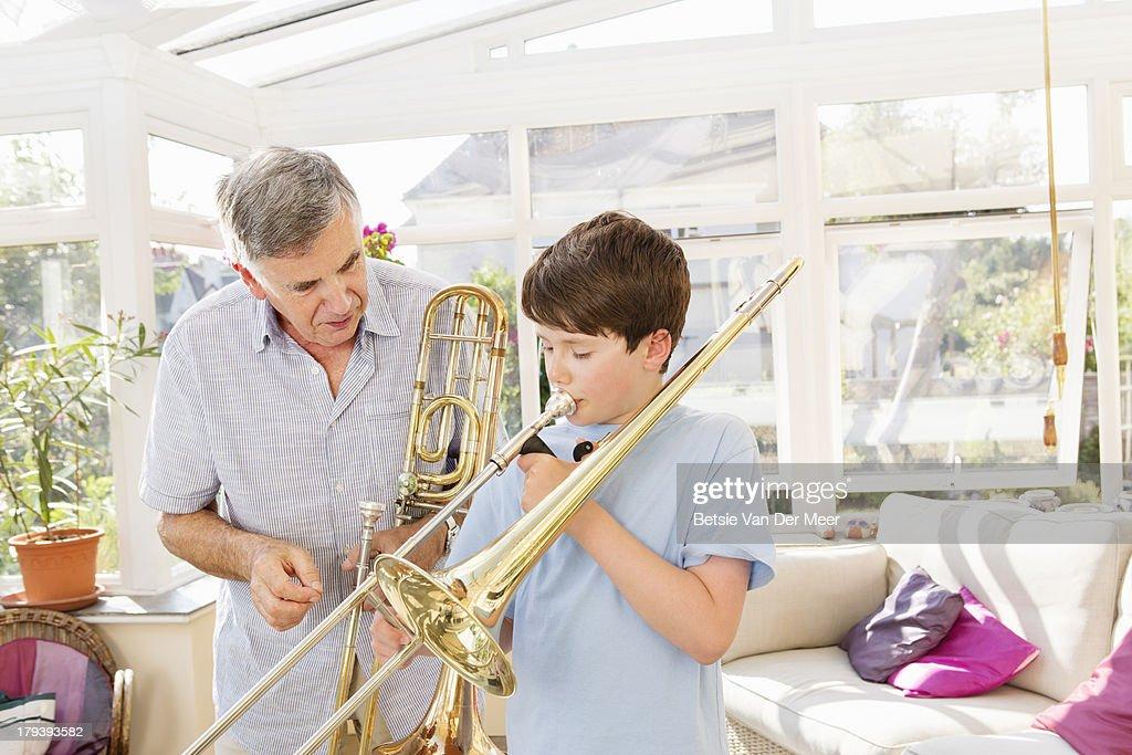 Grandfather teaching grandson to play trombone. : Stock Photo