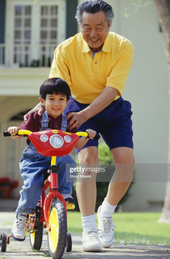 Grandfather teaching grandson (3-4) to ride bicycle in garden : Stock Photo