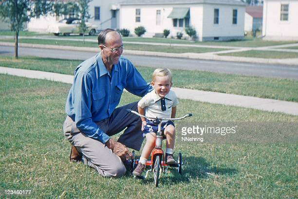 grandfather teaching grandson to ride tricycle 1953, retro