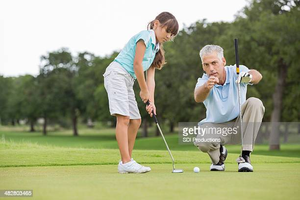 Grandfather teaching little girl to play golf