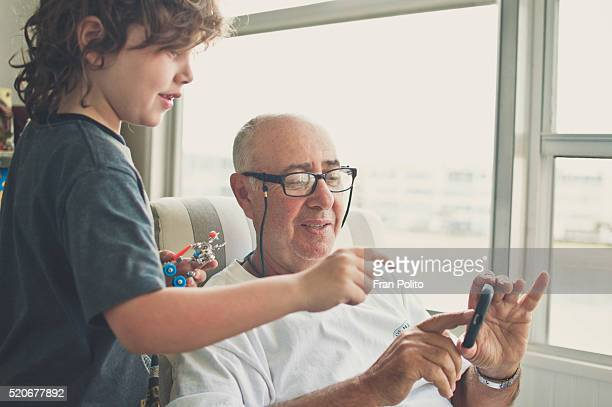 Grandfather using a smart phone with his grandson.