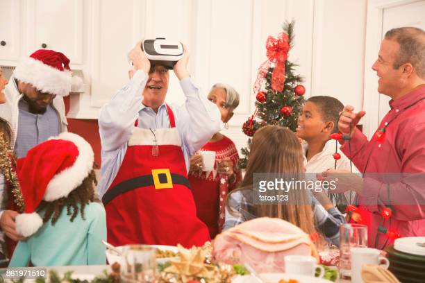 Grandfather using virtual reality technology at family Christmas party.