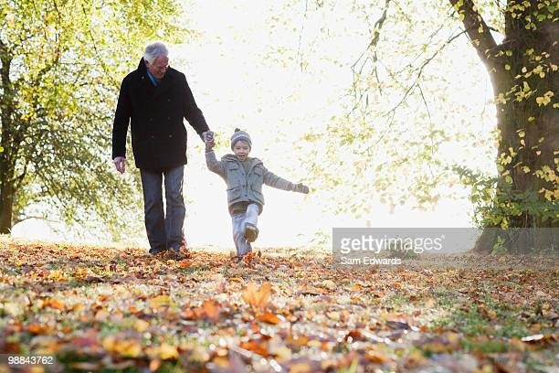 Grandfather walking outdoors with grandson in autumn