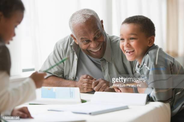 Grandfather watching grandchildren do homework