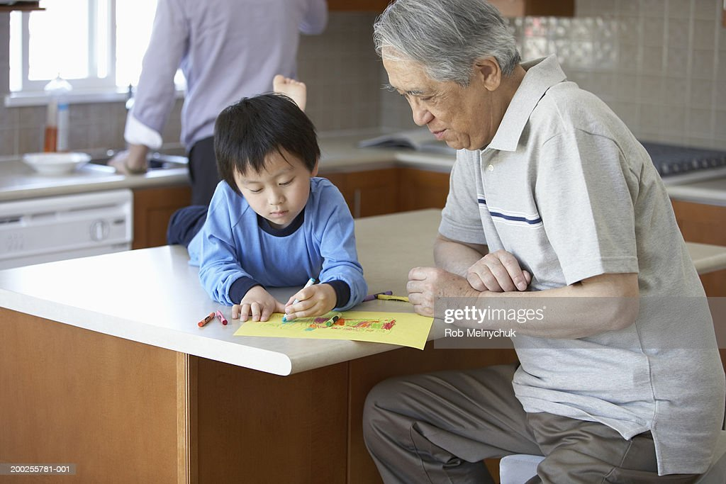 Grandfather watching grandson (3-5) draw with crayons in kitchen : Stock Photo