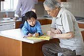Grandfather watching grandson (3-5) draw with crayons in kitchen