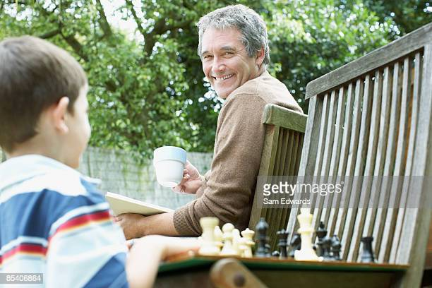 Grandfather watching grandson play chess
