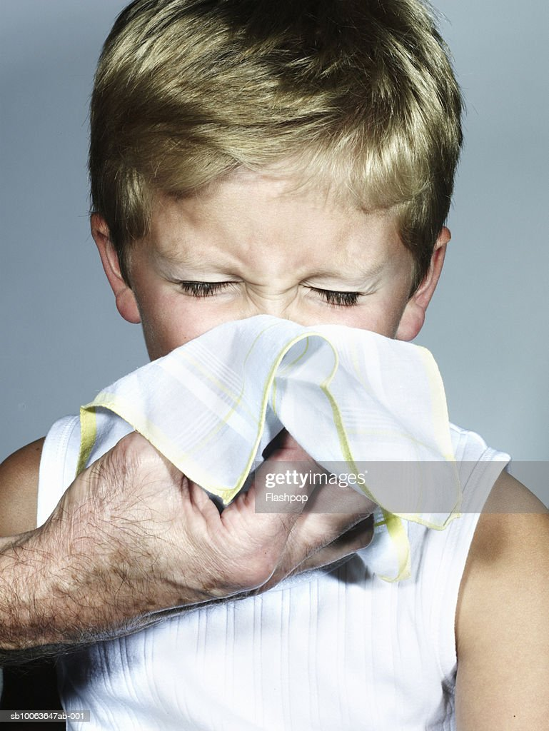 Grandfather wiping grandson's (6-7) nose, close-up : Stock Photo