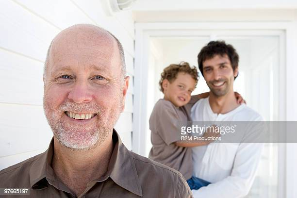 Grandfather with father and son behind, Portrait