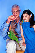 Grandfather with granddaughter and parrot