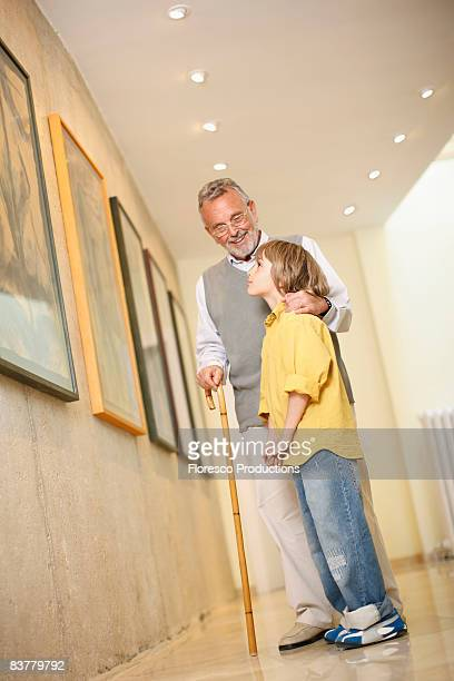 Grandfather with grandson in art gallery