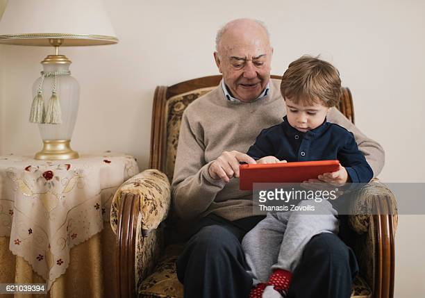 Grandfather with his grandson using a digital tablet
