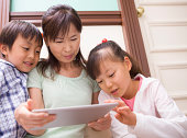 Grandma and children are using a tablet PC
