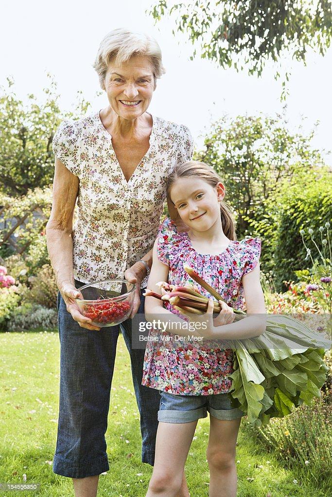 Grandma and grandchild holding berries and rhubarb : Stock Photo