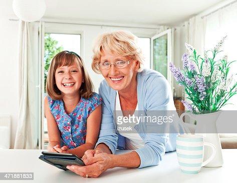 Grandma and grandchild with e-reader