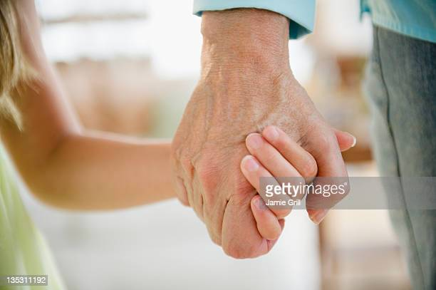 Grandma and granddaughter holding hands, close up