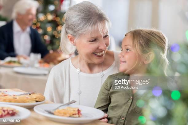 Grand-mère et sa petite-fille partagent une tranche de tarte au moment de Noël