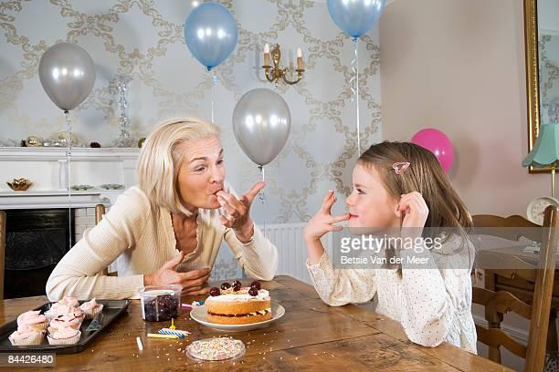 Grandma and granddaughter tasting birthday cake.