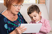 Grandma and grandson looking at tablet computer together at home